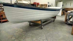 the hull on the building cradle.  the cart is heeled so it is easy to move the boat around the shop.