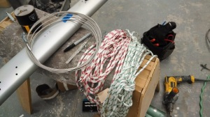 Here are the main halyard (white w/green fleck), jib halyard (white w/red fleck) and the old backstay wire used to pull the lines through the mast.