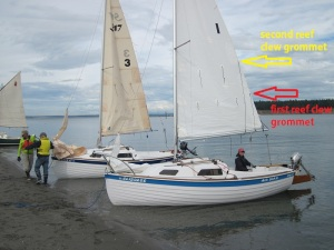 The arrows point to the clew reefing grommets.